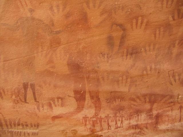 Большая фигура на фоне отпечатков рук и ног